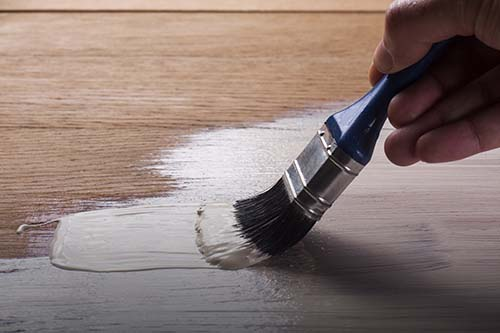 applying varnish paint on a wooden surface